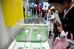 "December 13, 2012, Tokyo, Japan - A visitor sees the mini solar panels at Eco-Products Exhibition. The Eco-Products Exhibition is one of the biggest environmental issues in Japan, drawing more than 180,000 business people and consumer exhibitors. The theme of this year is ""The Greener, The Smaller - The Future We Will Choose"", the exhibition will be held from December 13th to 15th in Tokyo Big Sight.(Photo by Rodrigo Reyes Marin/AFLO).."