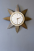 In the living room a retro clock in the shape of a starburst has been arranged against a grey-painted wall