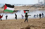 Palestinian demonstrators protest on the beach along the northern Gaza border, across from the Israeli settlement of Kibbutz Zikim, on  February 19, 2019, as part of weekly maritime protests against the naval blockade of the coastal enclave. At least 20 Palestinians were injured as Israeli forces suppressed the 24th naval march along the northern besieged Gaza Strip, on Tuesday afternoon. Photo by Ashraf Amra