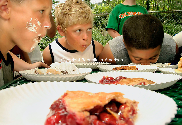 PLYMOUTH, CT--27 JULY 2006 -072706JS01-Stephen Brown, left and Eric Mensel, center, look around the table to see how the competition is faring as Marlando Campbell, right, continues to eat his pie during the Plymouth Park and Recreation Department's pie eating contest held Thursday at Veterans Memorial Par in Plymouth. The three were competing in the 10 year-old division.  -Jim Shannon Republican-American