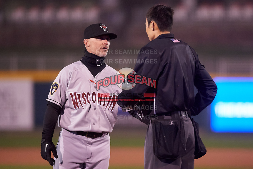 Wisconsin Timber Rattlers manager Matt Erickson (8) discusses a call with umpire Jae-Young Kim during a Midwest League game against the Lansing Lugnuts at Cooley Law School Stadium on May 2, 2019 in Lansing, Michigan. Lansing defeated Wisconsin 10-4. (Zachary Lucy/Four Seam Images)