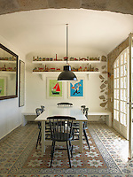 A contemporary table and chairs contrast with a tiled mosaic floor in the dining room