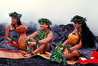 Three hula kahiko (ancient style) dancers, one male and two females, sit on a woven lauhala mat on top of black hardened lava at Puna on th eBig Island of Hawaii. Volcanic mist rises in the background.