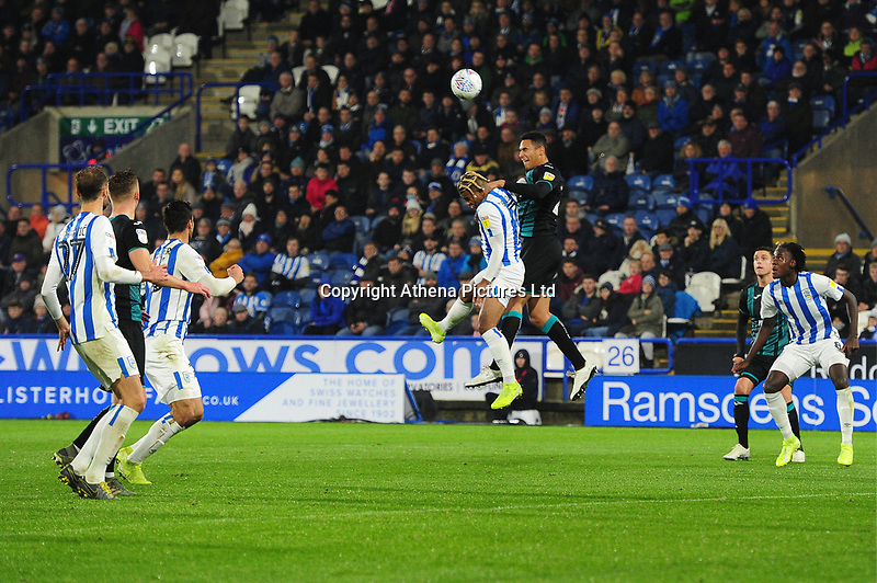 Ben Cabango of Swansea City battles with Juninho Bacuna of Huddersfield Town during the Sky Bet Championship match between Huddersfield Town and Swansea City at The John Smith's Stadium in Huddersfield, England, UK. Tuesday 26 November 2019