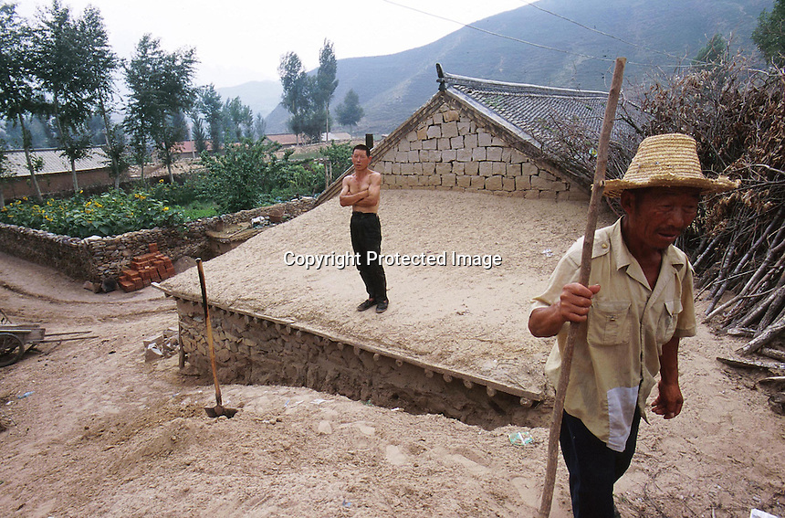 Moving sand swamps a village house despite the efforts of locals to dig it out in LangTou Gou, Fang Ning, China.  Droughts and increasing desertification are causing ever-greater environmental problems in northern China...WONG / SINOPIX