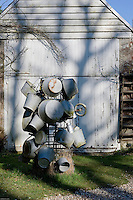 A collection of old zinc buckets, basins and watering cans takes on a sculptural form in the garden of a restored gamekeeper's cottage in Le Touquet, France