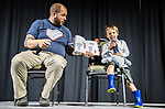 Jacob Hagman, School of Nursing's Academic Advisor,  reads a book on stage with his son during the 'Talent' portion of the 2018 Falculty Pageant.