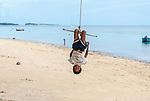 Boy playing on a swing at dusk in Funafuti, Tuvalu