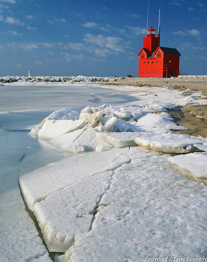 Allegan County, MI:  Red lighthouse at Holland Harbor with ice sheets on the shore of Lake Michigan