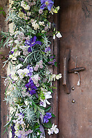 Detail of a flower arrangement of sweet peas and rosemary hung around the front door
