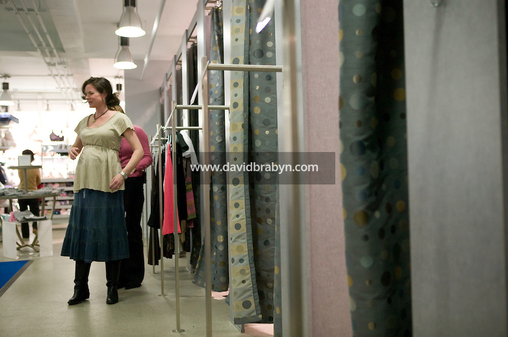 A pregnant woman tries on clothes at the Destination Maternity store on Madison Avenue in New York City, USA, 10 March 2006.