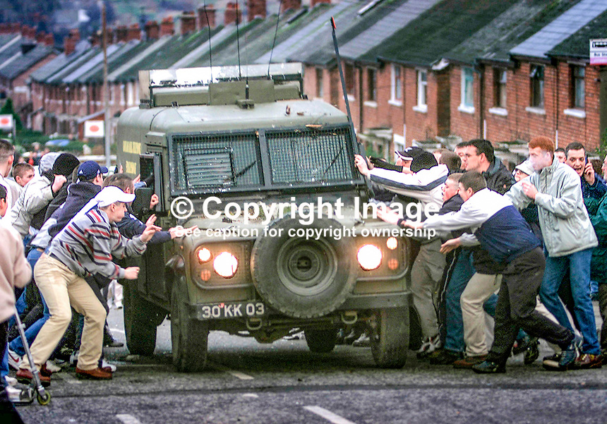 Republican rioters in Alliance Avenue, Ardoyne, Belfast, N Ireland, UK, attempt to overturn a British Army Landrover. January 2002. 200201024. <br /> Copyright Image from Brendan Murphy, c/o Irish News, 113 Donegall Street, Belfast, UK, BT1 2GE...Tel: +44 28 9032 2226.Email: photographers@irishnews.com..IMPORTANT: If you wish to use this image or any other of my images please go to www.victorpatterson.com and click on Terms &amp; Conditions. My terms are exactly the same as those for Victor Patterson. Then contact me by email or phone with the reference number(s) of the image(s) concerned.