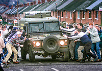 Republican rioters in Alliance Avenue, Ardoyne, Belfast, N Ireland, UK, attempt to overturn a British Army Landrover. January 2002. 200201024. <br /> Copyright Image from Brendan Murphy, c/o Irish News, 113 Donegall Street, Belfast, UK, BT1 2GE...Tel: +44 28 9032 2226.Email: photographers@irishnews.com..IMPORTANT: If you wish to use this image or any other of my images please go to www.victorpatterson.com and click on Terms & Conditions. My terms are exactly the same as those for Victor Patterson. Then contact me by email or phone with the reference number(s) of the image(s) concerned.