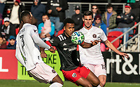 WASHINGTON, DC - MARCH 07: Ola Kamara #9 of DC United caught between Andrés Reyes #3 of Inter Miami and Dylan Nealis #18 during a game between Inter Miami CF and D.C. United at Audi Field on March 07, 2020 in Washington, DC.