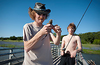 James O'Malley (cq, left) unhooks a small catfish caught by Neil O'Malley (cq, 16) on Lake Buchanan off Ranch Road 2341 in Hill Country near Burnet, Texas, April 25, 2010. ..PHOTOS/ MATT NAGER