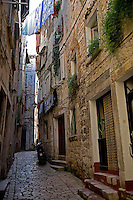 The seaside town of Rovinj on the Istrian peninsula of Croatia provides ancient houses tightly grouped in twisting narrow backstreets .