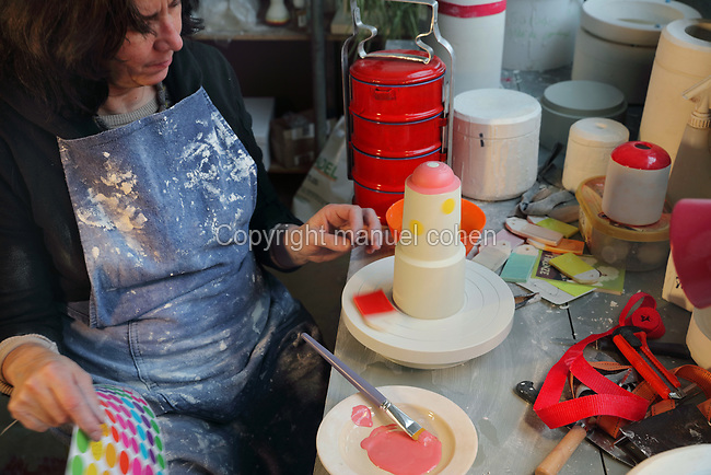 Ceramicist Valeria Polsinelli decorating a vase with coloured glazes on a turntable, photographed in 2017, in her studio in Montreuil, a suburb of Paris, France. Polsinelli creates everyday vessels, water jugs, jewellery and figurines and stoppers of female busts, with features and hairstyles from various world cultures. Picture by Manuel Cohen