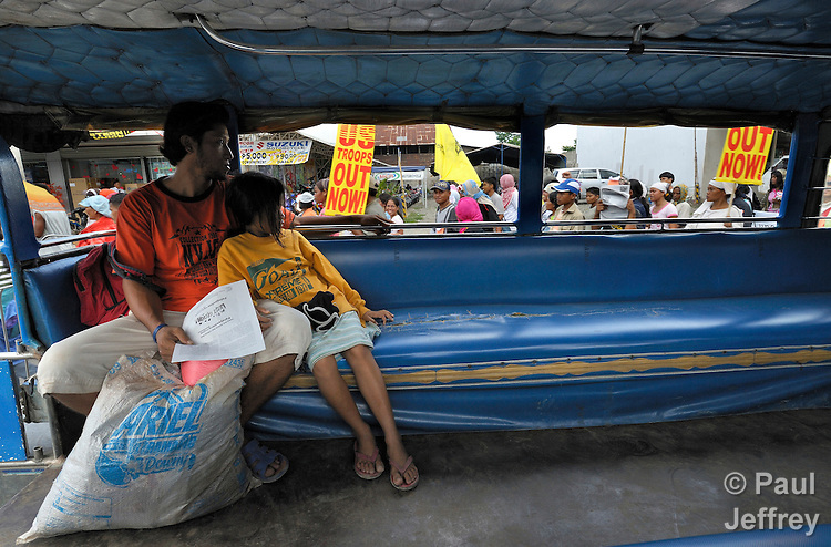 Passengers in a typical Filipino jeepney observe protestors marching through the streets of Cagayan de Oro, in the southern Philippines region of Mindanao, on February 18 to protest against the presence of U.S. troops in the war-plagued area. This protest, along with demonstrations in other cities and towns throughout Mindanao, marked the beginning of two weeks of joint U.S. training exercises with the Philippine military. U.S. troops have also operated permanently in Mindanao since 2002 in operations against Muslim insurgents.