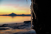 An icicle hangs from a large chunk of ice deposited on Alaska's Kenai Beach by Cook Inlet's mammoth tide change.