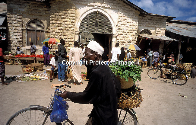 COTANZA35094.Country. Tanzania. Zanzibar market. Man pushing bicycle, basket with green leafy vegetable. Variety of fruits and vegetables. Vendors, Muslim..©Per-Anders Pettersson/iAfrika Photos