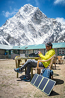 A trekker sits at a Nepali guesthouse beneath the mountain Cholatse, using a solar panel to charge batteries. Dzongla, Nepal.
