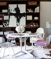 The dining room has Harry Bertoia chairs with lilac cushions set around a white table. In the background stands an open display unit with shelves.