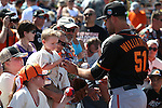SF Giants' Mac Williamson autographs a ball for Joseph Silva and his son JoJo, 4, before a spring training game in Peoria, Ariz., on Wednesday, March 16, 2016. <br />