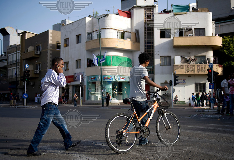 Refugees from Eritrea walk down a street in Tel Aviv. One is speaking on a mobile phone, the other is pushing a bicycle.