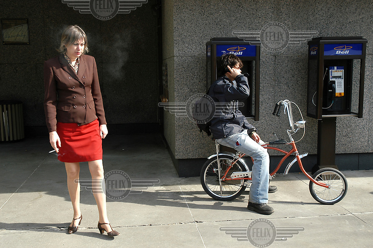 A woman smokes in front of the Place Alexis Nihon on Boulevard de Maisonneuve in Montreal. Behind her a man sitting on a childs bicycle makes a call on a mobile...