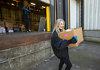Brooklyn Thompson, 14, of Bentonville carries an order to a car Saturday, March 21, 2020, at Kimball and Thompson Produce in Lowell. The business supplies fresh produce to the food service industry, including public schools, restaurants and hotels. With many of their usual clients closed due to the covid-19 pandemic, owner Chris Thompson says they are adapting to get their inventory directly to consumers who need it at wholesale prices. Thompson says he is also reaching out to the Northwest Arkansas Food Bank to make sure nothing goes to waste. <br /> <br /> The business began selling to the public Friday morning, and many shelves were already bare Saturday. Thompson says they will be working to keep their inventory updated as they navigate the temporary change to their business model. <br /> <br /> Staff and family members are pitching in to help fill orders curbside while minimizing personal contact and practicing strict sanitizing measures. Customers are asked to place orders ahead of time by calling 479-872-0200 or emailing orders@ktproduce.com. Pickup times are Monday through Saturday from 9 a.m. to 4 p.m., and Sunday from 11 a.m. to 2 p.m. at 305 S. Lincoln St. in Lowell. <br /> <br /> Check out nwaonline.com/200322Daily/ for today's photo gallery.<br /> (NWA Democrat-Gazette/Ben Goff)