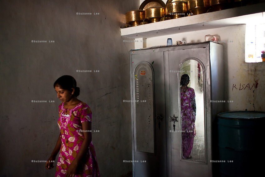 "Shardaben's eldest daughter, Lakshmi (18) walks out of a room. 200,000 rupees out of the money Shardaben earned from surrogacy will soon be given to Lakshmi's husband-to-be as her dowry. ..Shardaben Kantiben, 31; Husband is Kantibhai Motibhai (37).3 children --- 2 girls -  Usha(15) and Lakshmi (18, in pink); 1 boy, Chintan (17).- Education costs for all three come to Rs. 15,000 per year.- Shardaben was a two-time surrogate. First time she gave birth to twin girls for a Taiwanese couple and the second time a boy for an Indian couple from America (photo on TV set because she's proud that it was a boy).- The second time she became emotional and they got a gold ring of Rs. 1,500 made for the boy, which they presented to the biological parents. They are not in touch with either couple..- From the two surrogacies, they earned a little over 700,000rupees..-200,000rupees will be given as dowry for Lakshmi's wedding..- They leased agricultural land (Rs. 2 lakhs for five years) which earns them Rs. 60,000-70,000 a year; they bought two buffaloes worth Rs. 60,000 and make almost 6000-7000 per month selling milk; they bought a motorbike for Rs. 25,000; they put some money into house repairs and the construction of toilets, and opened a fixed deposit in Shardaben's name for Rs. 1.5 lakh and one in the name of their son, Chintan, for Rs. 25,000..Quotes..""Everyone says they'll keep in touch and take down addresses and phone numbers but nobody looks back. And I guess it works well. Our main interest was in the money. Their main interest is in the baby."" - KantiBhai.""Their rules apply at the surrogate house. It does curtail the freedom. When I used to go, everybody would just be lying. They count the days when they can go back."" - Kantibhai.""Ours is natural birth but surrogacy is a man-made pregnancy. There's a lot of risk. She must have taken at least 300 injections."" - Kantibhai of his wife...The Akanksha Infertility Clinic is known internationally for its surrogacy program and cu"