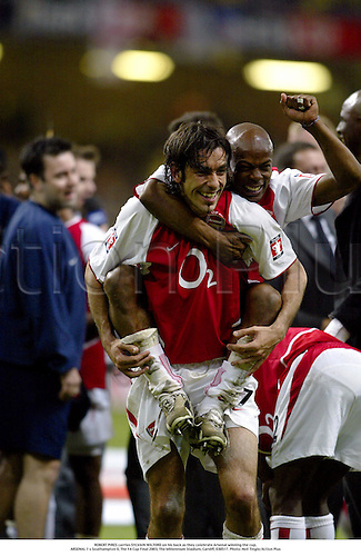 ROBERT PIRES carries SYLVAIN WILTORD on his back as they celebrate Arsenal winning the cup, .ARSENAL 1 v Southampton 0, The FA Cup Final 2003, The Millennium Stadium, Cardiff, 030517. Photo: Neil Tingle/Action Plus...Association Football soccer.Footballer footballers.celebrates celebrating celebration celebrations joy.....