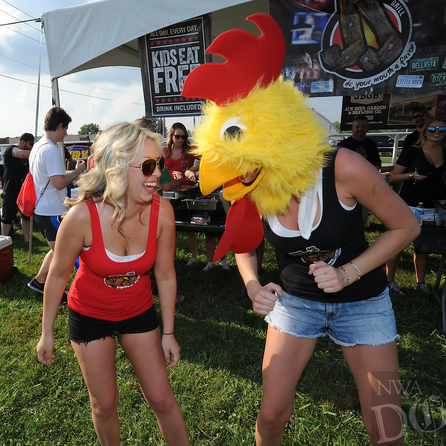 NWA Democrat-Gazette/ANDY SHUPE<br /> Jordan Rackleff (left) of Siloam Springs laughs Saturday, June 11, 2016, as she dances with fellow J.J.'s Grill waitress Ruth Davis of Rogers while they try to bring patrons to the restaurant's booth during the 12th annual Wingfest at Parsons Arena in Springdale. The fundraising event features chicken wing competition between 11 area merchants, music and games to benefit the Springdale Kiwanis Club and Kendrick Fincher Hydration for Life.