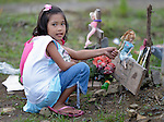 A girl plays with a doll that marks the grave of a friend in a church yard in the city of Palo, in the Philippines province of Leyte, where typhoon Haiyan killed hundreds of people in November 2013. The storm was known locally as Yolanda.