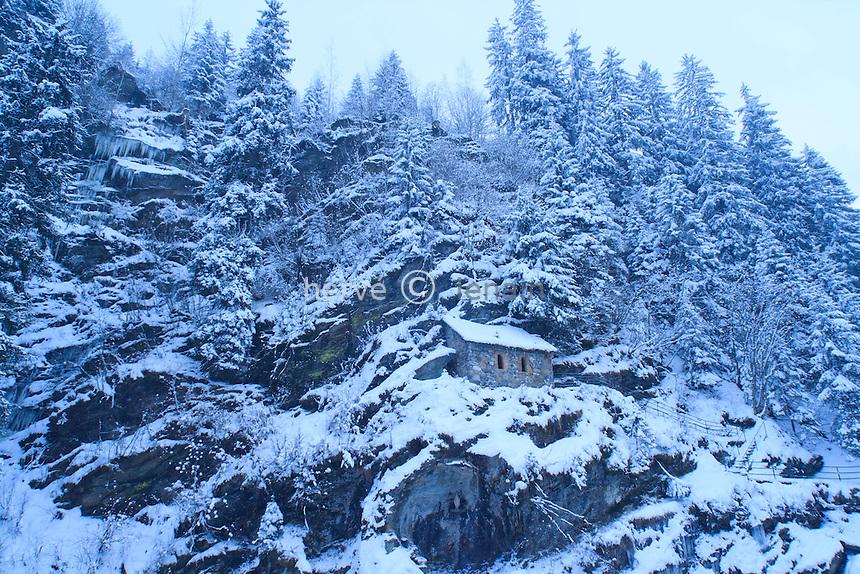 France, Haute-Savoie (74), Les Contamines-Monjoie, la Sainte-Chapelle sous la neige, deux cents mètres en amont de la Chapelle Notre-Dame-de-la-Gorge, une petite chapelle bien singulière est accrochée au flanc de la paroi rocheuse, la construction primitive se trouvait à l'aplomb de celle que l'on découvre aujourd'hui, la tradition veut que le premier ermite qui se soit installé à la Gorge ait choisi ce site pour établir son ermitage, dès le Moyen-Age, la Sainte-Chapelle fut un lieu de pèlerinage fort prisé des habitants de la région, aujourd'hui encore, le 15 Août, jour de l'Assomption et le 8 Septembre, anniversaire de la Nativité de la Vierge, une procession conduit les fidèles de l'église de Notre-Dame de la Gorge à la Sainte-Chapelle, à l'issue de l'office // France, Haute Savoie , Les Contamines Monjoie, the St Chapel in the snow, two hundred meters upstream from the chapel Notre Dame de la Gorge, a very strange little chapel is hung on the side of the cliff, the original building was located directly above that which we find today, tradition dictates that the first hermit to be installed at the Gorge has chosen this site to build his hermitage, from the Middle Ages, the St Chapel was a very popular place of pilgrimage inhabitants of the region today, August 15, Assumption Day, and September 8, the anniversary of the Nativity of the Virgin in a procession led the faithful of the Church of Notre-Dame de la Gorge Sainte-Chapelle, after the Office