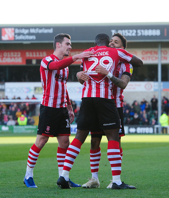 Lincoln City's Bruno Andrade, right, celebrates scoring the opening goal with team-mates Harry Toffolo, left, and John Akinde<br /> <br /> Photographer Chris Vaughan/CameraSport<br /> <br /> The EFL Sky Bet League Two - Lincoln City v Northampton Town - Saturday 9th February 2019 - Sincil Bank - Lincoln<br /> <br /> World Copyright &copy; 2019 CameraSport. All rights reserved. 43 Linden Ave. Countesthorpe. Leicester. England. LE8 5PG - Tel: +44 (0) 116 277 4147 - admin@camerasport.com - www.camerasport.com