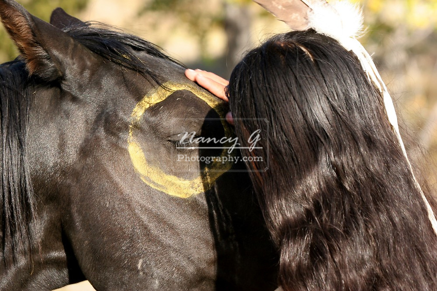 A young Native American Indian boy showing affection to his horse