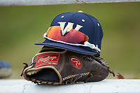 A Wingate Bulldogs cap sits on top of a Rawlings baseball glove prior to the game against the Concord Mountain Lions at Ron Christopher Stadium on February 1, 2020 in Wingate, North Carolina. The Bulldogs defeated the Mountain Lions 8-0 in game one of a doubleheader. (Brian Westerholt/Four Seam Images)
