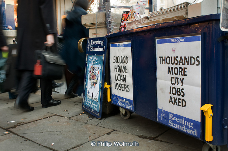 Newspaper billboard advertising 'Thousands more City Jobs Axed', central London.