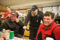 Aaron Burmeister, Race Judge Mark Nordman, and Ramy Brooks take in a laugh while hanging out inside the community center at Takotna