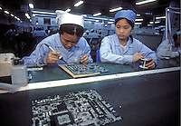 Two female workers assemble circuit boards at a Lenovo Computer factory in Guangzhou, China. Lenovo Group (was formerly known as Legend) is China's largest maker of personal computer. Lenovo announced a definitive agreement under which Lenovo will acquire IBM's Personal Computing Division to form the world's third-largest PC business, bringing IBM's leading enterprise-class PC technologies to the consumer market and giving Lenovo global market reach beyond China and Asia..13-MAR-01