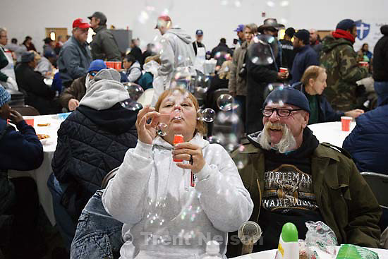 Brenda Crest blows bubbles next to her husband Charlie Crest, at a dinner at the Christian Life Center. The Crests were just married Friday, Christmas morning. The Salt Lake City Mission planned on serving 2,000 ham and turkey suppers this year, more than ever before, at the Christian Life Center. Toys, personal care items and warm clothes were distributed all day. Friday, December 25, 2009.