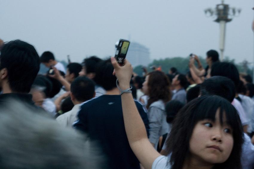 Une jeune fille prend une photo du drapeau et soudain se retourne vers le centre de la place.... (voir photo suivante)