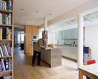 Ann Grut reading a magazine in her contemporary kitchen/dining area