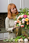 Mature woman arranging flower bouquet
