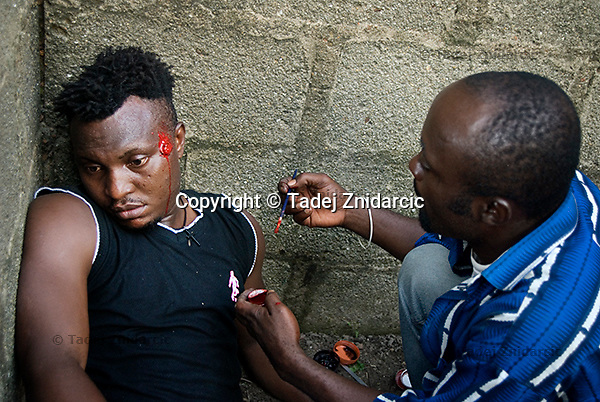 Make-up artist Kpoyi Creation (right) preparing a gun-shot wound on the face of an actor playing a vigilante on the set of a Nollywood movie production. Vigilantes, guns and murder in Nollywood movies reflect the often violent Nigerian reality.