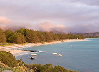 Another famous windward Oahu sunrise turns the clouds, trees, and sand of Kailua Beach pink.  Small boats at anchor await another day's fishing adventure.