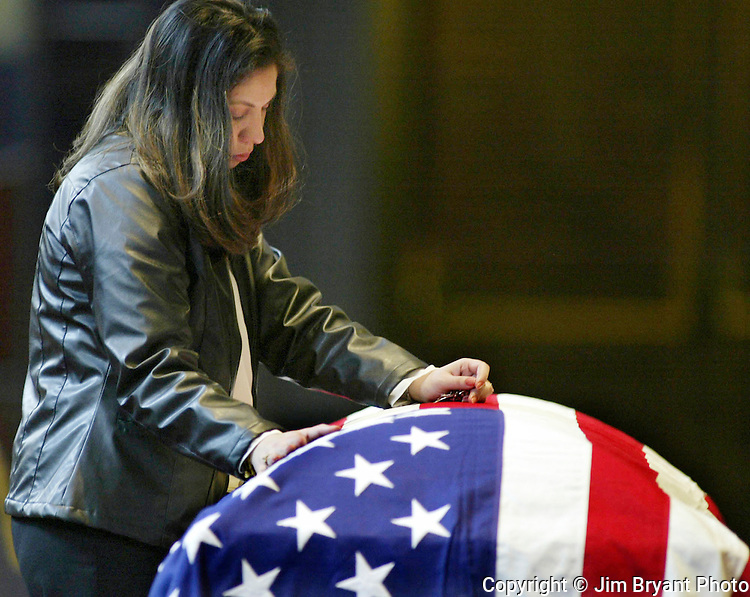 Michele Bunda touches the flag-drapped coffin of her late husband Staff Sgt. Christopher Bunda during the Rosary before Mass at the Holy Trinity Roman Catholic Church in Bremerton, WA., on Friday, Feb. 20, 2004. Staff Sgt. Bunda, from Bremerton, WA., was killed on Jan. 25, 2004 when a boat he was riding capsized on the Tigris River. Jim Bryant Photo