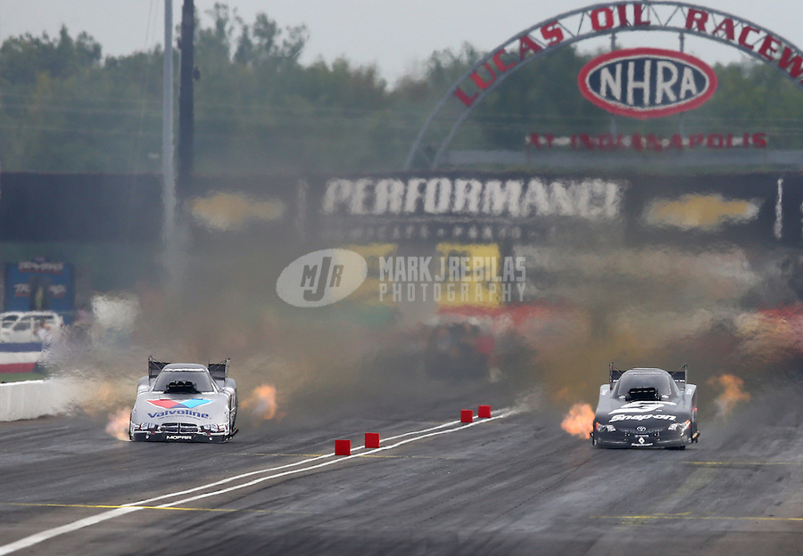 Aug 30, 2014; Clermont, IN, USA; NHRA funny car driver Cruz Pedregon (right) races alongside Jack Beckman during qualifying for the US Nationals at Lucas Oil Raceway. Mandatory Credit: Mark J. Rebilas-USA TODAY Sports