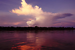A large anvil-shaped cumulus cloud, rising above rainforest along the shores of the Amazon River, is lit by evening light and reflecting in the calm waters of the river along its upper reaches in Peru.